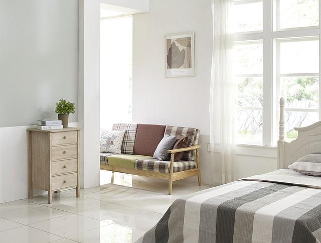 světlá ložnice vybavená dřevěným nábytkem