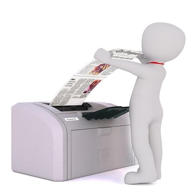 muž vytahující papír z tiskárny