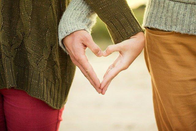 ruce muže a ženy, jak tvoří srdce, po krajích stojí jejich postavy